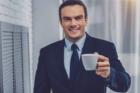 Cheerful attractive man smiling while offering you coffee in the office