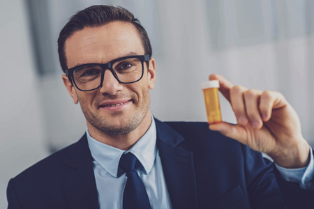 Joyful positive man smiling to you while showing a bottle with pills