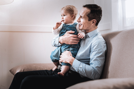 Fathers love. Positive delighted man holding his son while spending time with him together Stock Photo