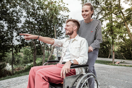 Happy couple. Joyful bearded man sitting in wheelchair and looking forward