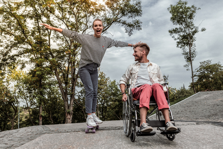 Joyful mood. Cheerful bearded man driving his wheelchair and looking at his partner
