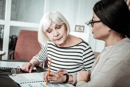 Ein Mal noch. Attraktive ältere Frau, die in der Nähe ihres Lehrers sitzt, während sie nach unten auf das Buch schaut