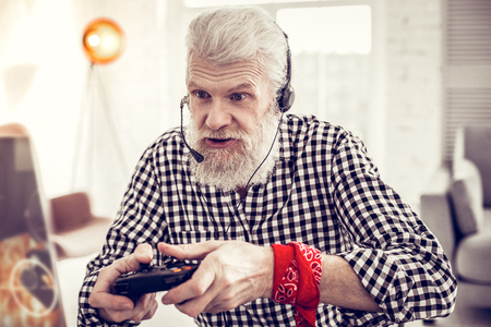 Being busy. Attentive mature man wrinkling forehead while staring at his gadget Фото со стока