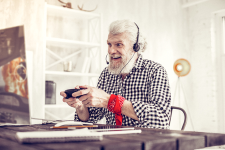So pleased. Cheerful male person wearing headphones while playing video game Фото со стока