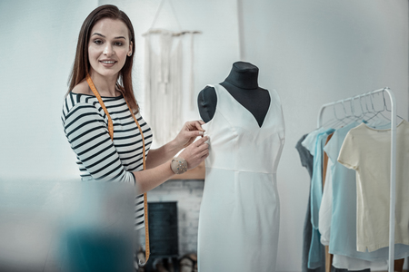 Near dress form. Dark-haired appealing fashion designer wearing striped shirt standing near dress form