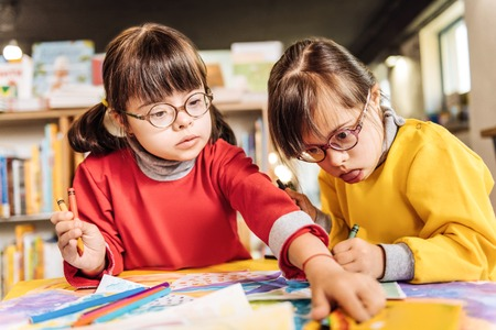 Helpful sisters. Cute appealing sisters having Down syndrome helping each other coloring pictures