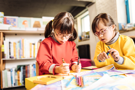 Holding crayons. Funny cute dark-haired sisters having Down syndrome holding crayons while drawing