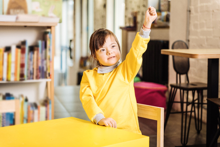 Sitting in kindergarten. Cute dark-eyed sunny child wearing yellow sweater sitting in kindergarten