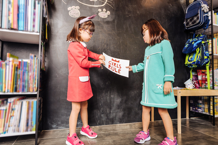 Bright sneakers. Cute dark-haired sunny children wearing bright sneakers standing near blackboard 免版税图像