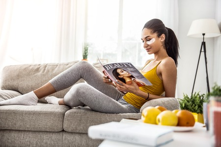 Press review. Cute brunette woman staring at magazine while lying on sofa Archivio Fotografico