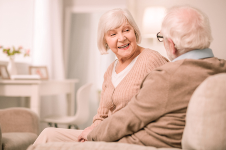 Pleasant smile. Attentive pensioner sitting in semi position and listening to his wife Imagens