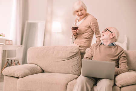 Join me. Happy old man laughing at joke while looking at his wife