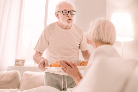 Adulthood love. Pleased grey-haired male person holding tray with food and looking at his wife
