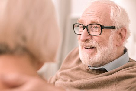 Handsome pensioner. Pleased bearded man wearing glasses, sitting near his wife Stok Fotoğraf