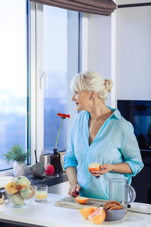 Such a beautiful view. Joyful aged woman looking into the kitchen window while holding an orange half