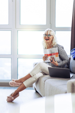 So much fun. Delighted nice woman putting a book to herself while enjoying it Stock Photo