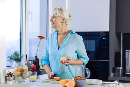Favourite fruit. Positive joyful woman smiling while holding an orange half