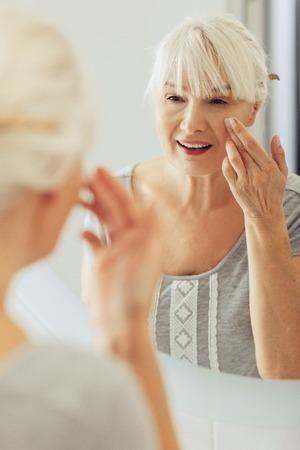 Reife Haut. Schöne alte Frau, die sich um ihre Haut kümmert, während sie im Badezimmer ist Standard-Bild