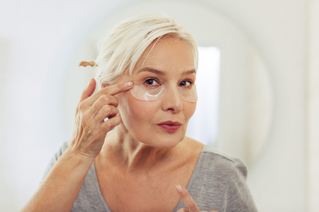 Gesichtsmaske. Nette ältere Frau, die mit Augenklappen steht, während sie Müdigkeitszeichen loswird