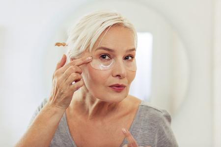 Máscara facial. Agradable anciana de pie con parches en los ojos mientras se deshace de los signos de fatiga