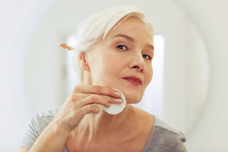 Face lotion. Pleasant good looking woman using a cotton pad while cleaning her face