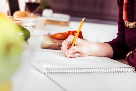 To do list. Busy woman leaning on table while creating plan for shopping