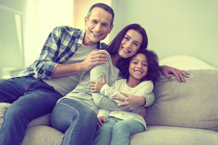 Best weekend. Happy mom, dad and little girl having a lot of fun together. Stock Photo
