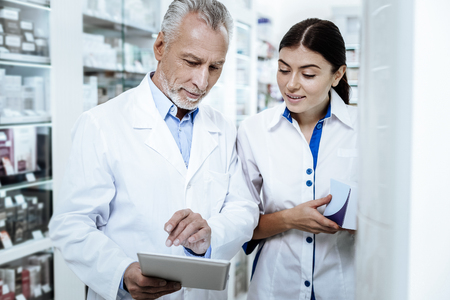 Conversation. Mature bearded man wearing a white coat discussing medicines with his young colleague Фото со стока