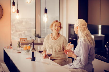 Positive aged women talking in the kitchen while drinking wine together Stock Photo