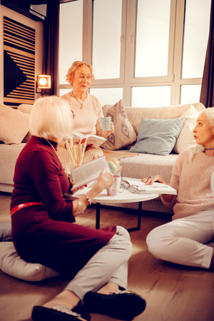 Modern poetry. Intelligent aged women speaking about literature while having a book club meeting
