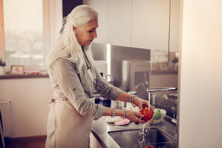 Absolutely clean. Pleasant aged woman standing near the sink while washing a red tomato