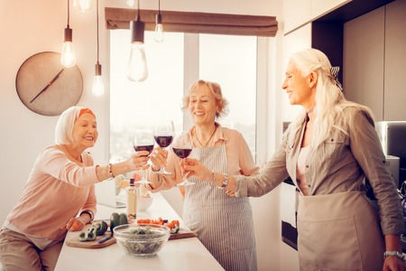 Small celebration. Happy cheerful women holding glasses of wine while having a celebration