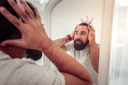 What a surprise. Nice surprised man looking into the mirror while waking up in the morning Stock Photo