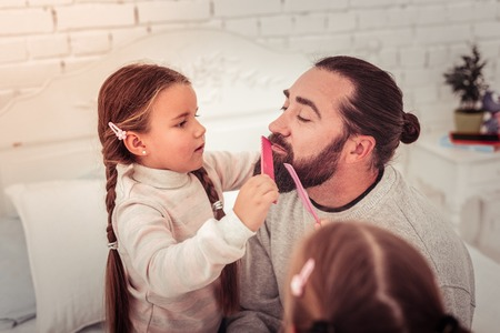 Beard grooming. Nice cute girl holding a comb while combing her dads beard