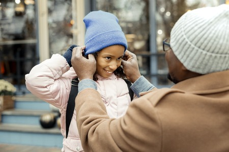Warm blue hat. Caring father putting warm blue hat on his cute daughter while walking outside Imagens