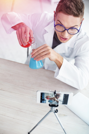 Video about chemistry. Top view of video blogger wearing white laboratory coat filming video about chemistry 版權商用圖片