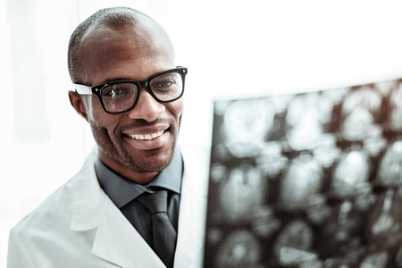 For you to understand. Cheerful international doctor wearing glasses while examining X-ray picture