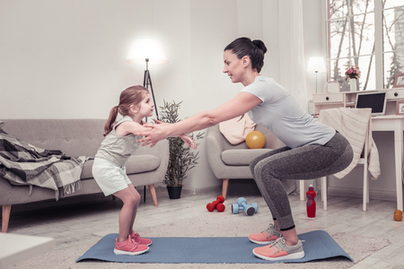 The best trainer. The mother teaching her daughter to do sit-ups Reklamní fotografie - 117793778