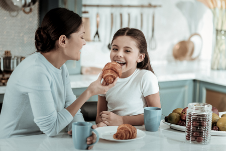 Nice taste. Careful pretty mother smiling while feeding a kid with a croissant 版權商用圖片