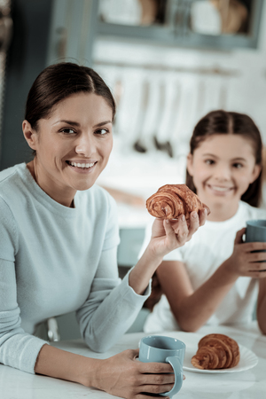 Good morning. Beautifuk pleasant lady eating croissants while having breakfast with a daughter
