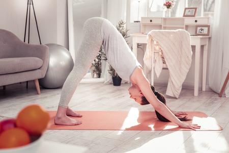 Downward-facing dog pose. The woman standing in the downward-facing dog pose while practising yoga Reklamní fotografie - 117794445