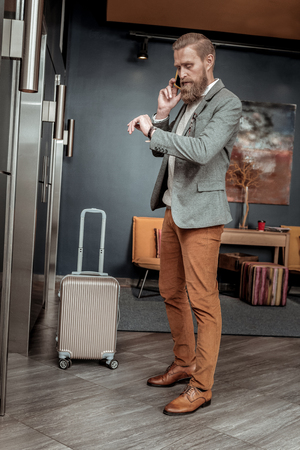 I am here. Stylish businessman bowing head and waiting for lift Stock Photo