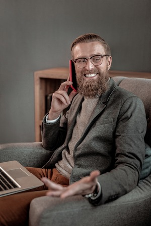 Joyful mood. Cheerful bearded man keeping smile on his face while sitting in cozy armchair 免版税图像