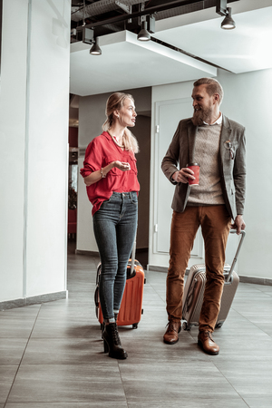 Best friends. Handsome bearded man holding suitcase and looking at his friend