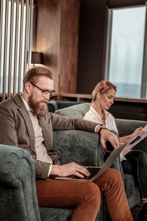 Business hall. Concentrated bearded man sitting in semi position and staring at screen of his gadget Stock Photo