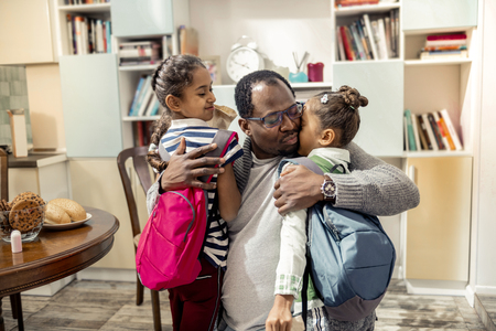 Little girls. Loving caring father hugging his cute little girls with backpacks going to school Imagens