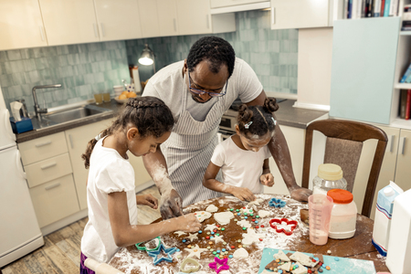 Decorating cookies. Top view of father and daughters decorating their Christmas cookies Banque d'images - 117795658