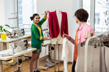 Friends. Two young asian fashion designers feeling wonderful in a workshop Banque d'images - 117795954