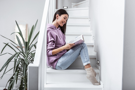Woman with book. Woman wearing jeans and warm socks reading book sitting on stairs at her home