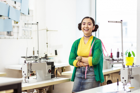 Happy girl. Young dark-haired asian designer wearing a green cardigan smiling happily